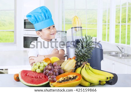 Portrait of a little boy wearing a cooking hat while making fruits juice in the kitchen at home - stock photo