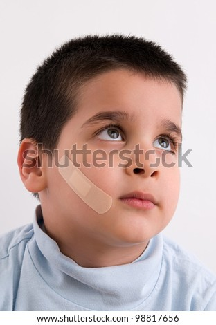 Portrait of a little boy with band aid on his face isolated on white background