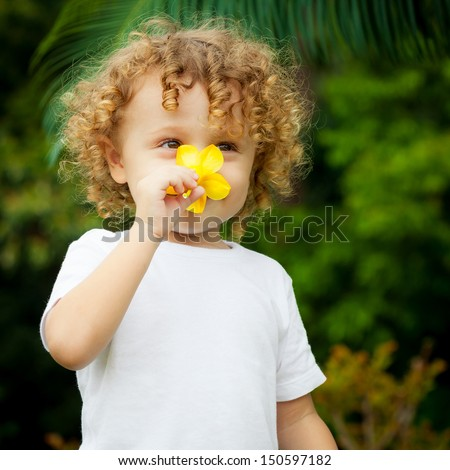 portrait of a little boy with flower in hand    - stock photo