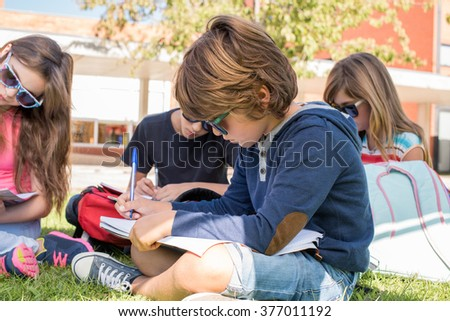 Portrait of a little boy with friends in school campus - stock photo