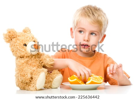 Portrait of a little boy with his teddy bear and oranges, isolated over white - stock photo
