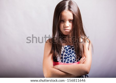Portrait of a little brunette with arms crossed and acting all mad on a white background - stock photo