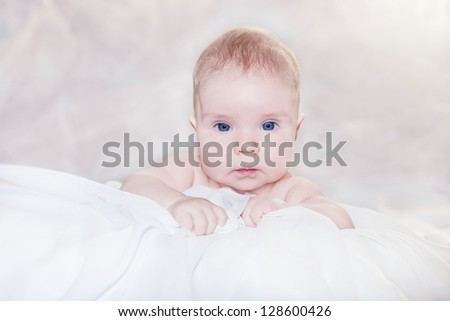 portrait of a little child lying on a blanket - stock photo