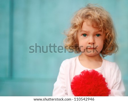 Portrait of a little cute curly girl outdoors near blue wall - stock photo
