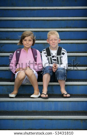 Portrait of a little girl and a little boy sitting on the steps of stairs - stock photo