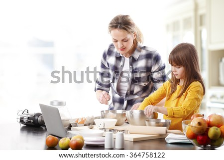 Portrait of a little girl and her mother sitting in the kitchen and baking together while using laptop to find recipe.  - stock photo
