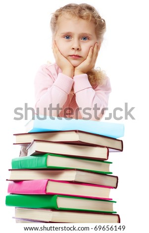Portrait of a little girl at a heap of books - stock photo