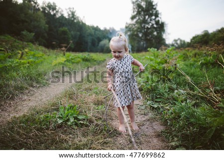Portrait of a little girl holding branches in summer field