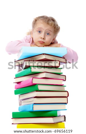 Portrait of a little girl holding on at a heap of books - stock photo