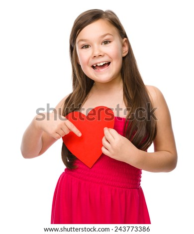 Portrait of a little girl holding red heart and pointing to it using index finger, isolated over white - stock photo