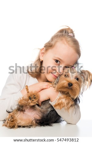 portrait of a little girl hugging Yorkshire Terrier on a white background