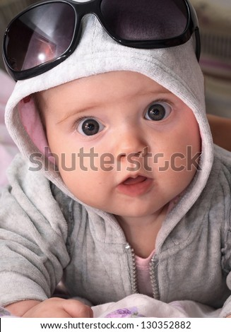 Portrait of a little girl in a hood and sunglasses