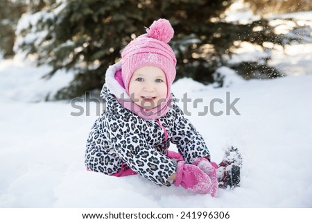 portrait of a little girl in a snowy forest - stock photo