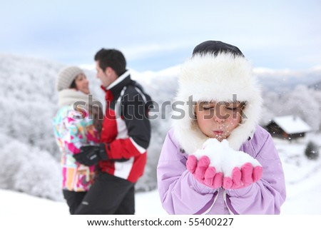 Portrait of a little girl in snowsuit blowing in snow - stock photo