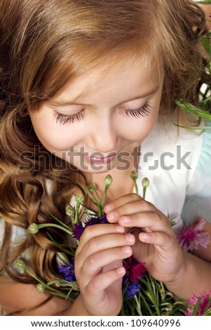 portrait of a little girl looking down with flowers
