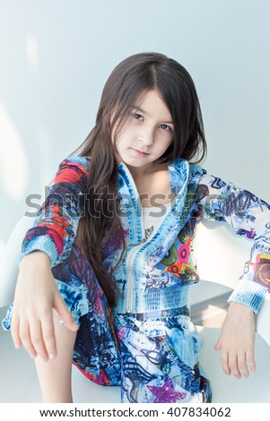 Portrait of a little girl of fashion baby on a white chair. Stylish little girl with long hair sitting on a white chair in front of the camera. Photo model child cool fashionable. Carefree fun - stock photo