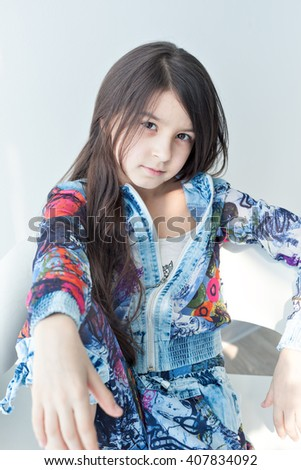 Portrait of a little girl of fashion baby on a white chair. Stylish little girl with long hair sitting on a white chair looking at the camera. Photo model child cool fashionable. Carefree fun - stock photo