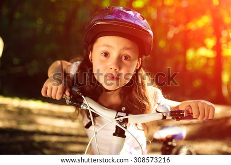 Portrait of a little girl on a bicycle in summer park against sunset - stock photo