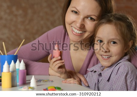 Portrait of a little girl painting with her mother