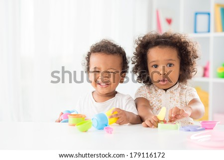 Portrait of a little girl posing at camera while her brother laughing and playing in the nursery - stock photo