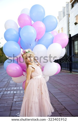 Portrait of a little girl princess with colorful balloons, outdoors street - stock photo