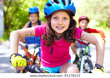 Portrait of a little girl riding her bike ahead of her friends - stock photo