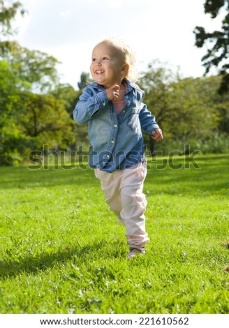 Portrait of a little girl running and playing outdoors - stock photo