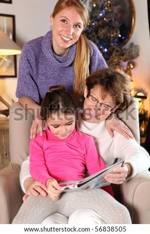 Portrait of a little girl sitting on a senior woman near a young woman - stock photo