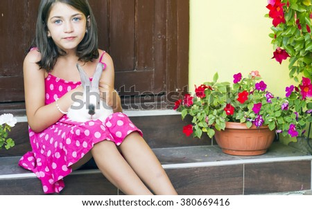 Portrait of a little girl standing on the stairs with rabbit on  - stock photo