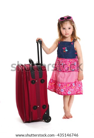 Portrait of a little girl standing with a suitcase on a white background