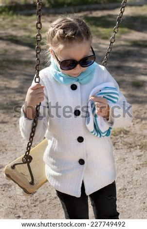Portrait of a little girl sunny autumn day ride on a swing in the park - stock photo