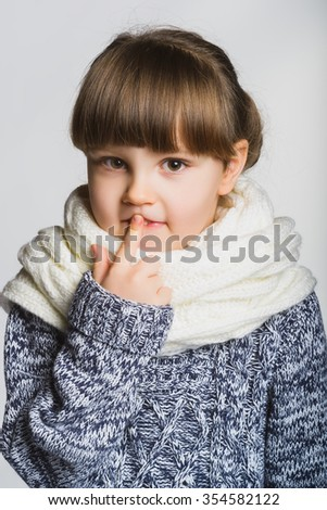 Portrait of a little girl thinking, over a gray background. - stock photo