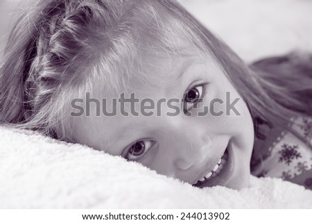 Portrait of a little girl who is lying. Happy smiling girl.