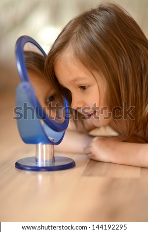 portrait of a little girl with a mirror on the floor