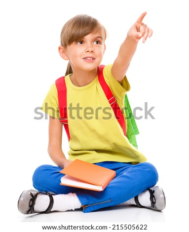 Portrait of a little girl with book, pointing up using her index finger, isolated over white - stock photo