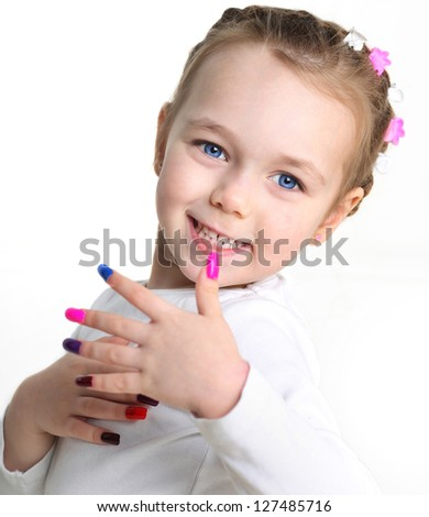 Portrait of a little girl with colorful nail polish on her hands - stock photo