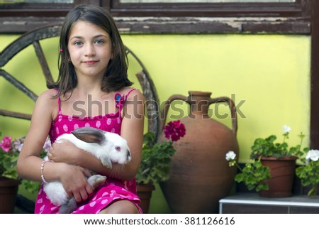 Portrait of a little girl with rabbit on her lap - stock photo