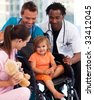 Portrait of a little patient with medical team in a wheelchair - stock photo