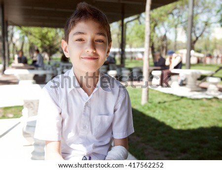 Portrait of a little schoolboy making his homework outdoors in summer.  - stock photo