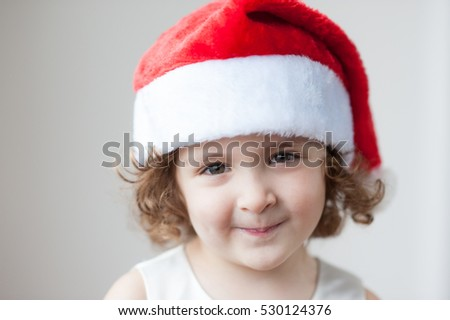 portrait of a little smiling curly-haired sweet girl in the Santa hat