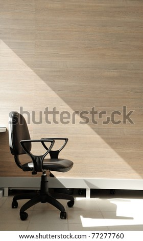Portrait of a lone office chair facing the right. Office background. - stock photo