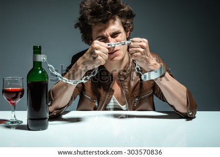 Portrait of a lonely and desperate drunk man trying to break the chains / photo of youth addicted to alcohol, alcoholism concept, social problem - stock photo