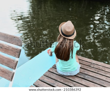 Portrait of a lonely girl in a hat near the water from the back - stock photo