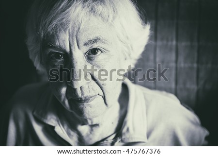 Portrait of a lonely gray-haired old woman. Black and white photo