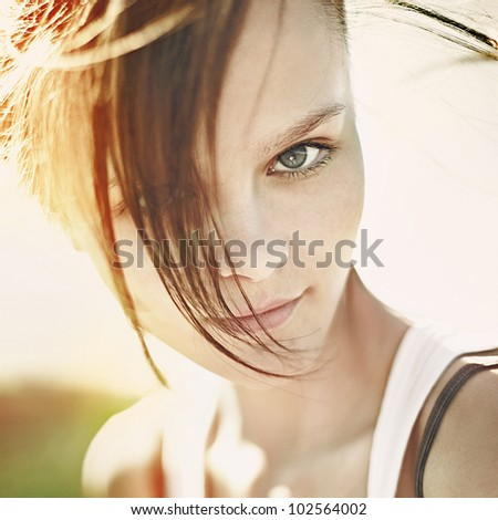 Portrait of a long-haired brunette with flying hair, the sun, summer, nature - stock photo