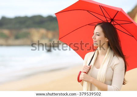 Portrait of a longing woman thinking and looking at horizon under a red umbrella on the beach with the sea in the background - stock photo