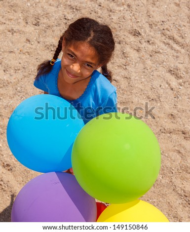 Portrait of a lovely african american girl with balloons - stock photo