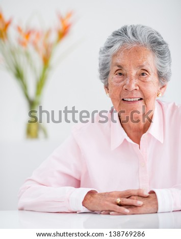 Portrait of a lovely elder woman at home smiling - stock photo