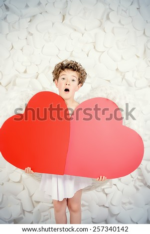 Portrait of a lovely emotional little boy in a costume of angel holding red hearts. Cupid. Valentine's day. - stock photo