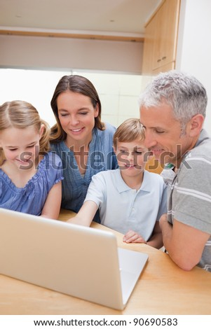 Portrait of a lovely family using a notebook in their kitchen - stock photo